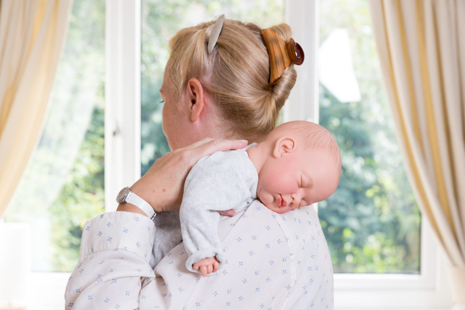 blonde woman holding a baby over her shoulder in order to wind a baby.