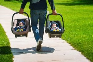 baby twins in car seats being carried by dad