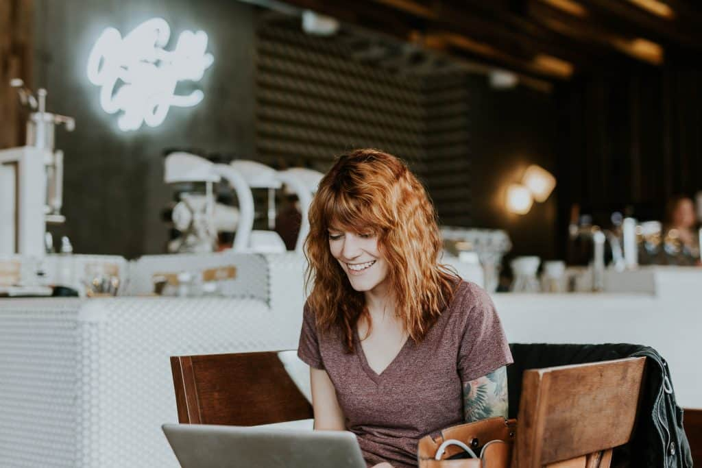 woman looking at laptop sitting at table wondering what is a WordPress plugin?
